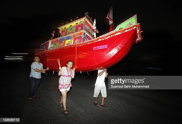 Members of the Chinese ethnic community carry a papermade ship during the Chinese Hungry Ghost Festival on August 22 2010 in Shah Alam Malaysia The...