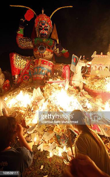 Members of the Chinese ethnic community perform prayers at a burning statue of the Chinese deity Da Shi Ye or Guardian God of Ghosts during the...