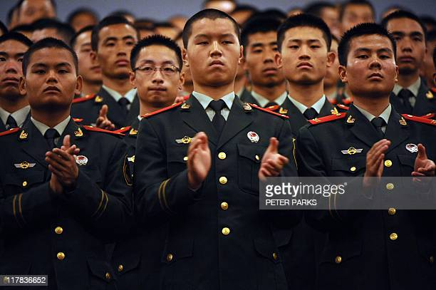 Members of the Chinese military applaud after Chinese President Hu Jintao gave a speech inside the Great Hall of the People in Beijing as part of...