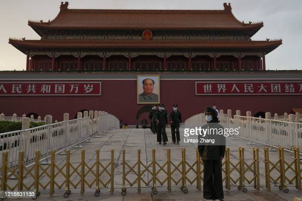 Members of the Chinese People's Armed Police wears a protective mask march through Tiananmen Gate during the closing meeting of the third session of...