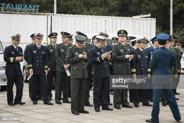 Members of the Chinese People's Liberation Army check their smartphones as they line up outside the Beijing Exhibition Center for the 'Five Years of...