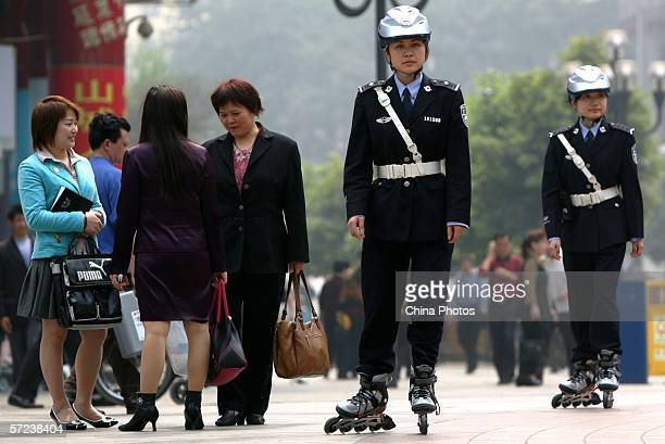 Members of the Chongqing Roller Skating Police Patrol Team perform their duty at the Jiefangbei Pedestrian Street April 3 2006 in Chongqing...