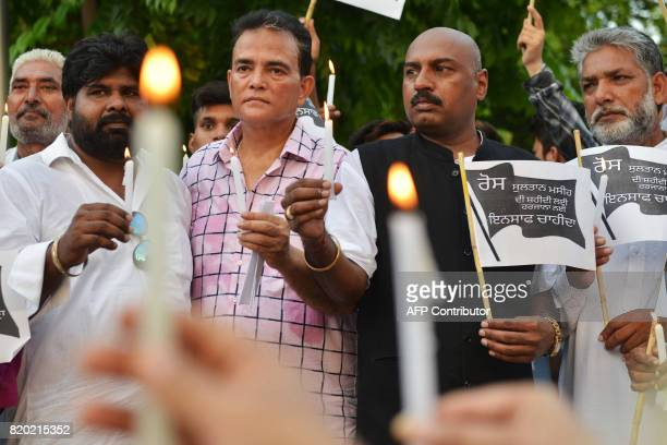 Members of the Christian community hold candles as they pay tribute to the pastor Sultan Masih who was shot dead by two assailants in Amritsar on...