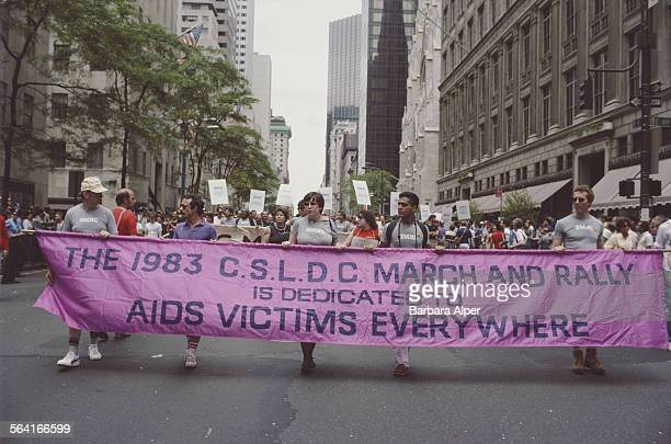Members of the Christopher Street Liberation Day Committee carry a banner through a street in New York City USA June 1983