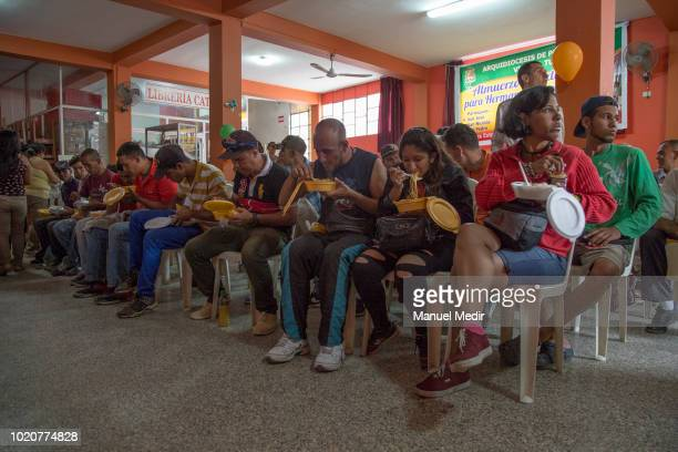Members of the church deliver the food to the Venezuelans at the church of San Nicolás on August 17 2018 in Tumbes Peru According to Peruvian...