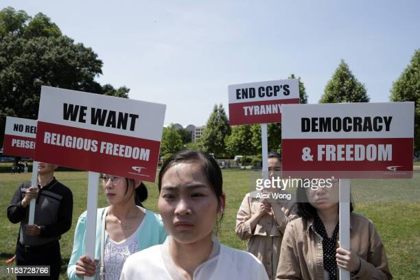 Members of The Church of Almighty God hold signs during a rally to commemorate the 30th anniversary of the Tiananmen Square massacre June 4 2019 at...