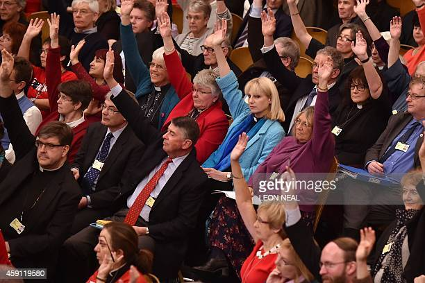 Members of the Church of England's Synod raise their hands as they formalise the vote on the consecration of women bishops in central London on...