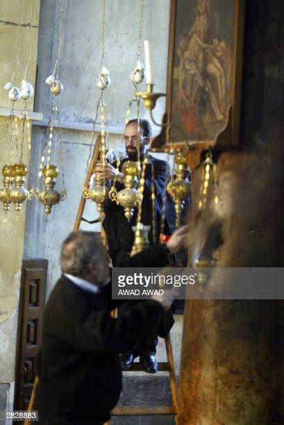 Members of the church polish the hanging lamps and dust the icons in the Church of the Nativity in the West Bank town of Bethlehem 23 December 2003...