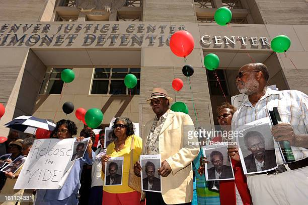 Members of the church stand together holding balloons of red green and black as they participate in the rally They chose those colors because they...