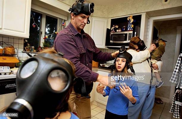 Members of the Cicero family trying on the gas masks they bought in their home kitchen preparing for bioterrorism following the September 11 attacks...