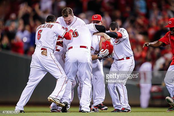 Members of the Cincinnati Reds celebrate with Devin Mesoraco of the Cincinnati Reds after hitting the game winning run during the ninth inning...