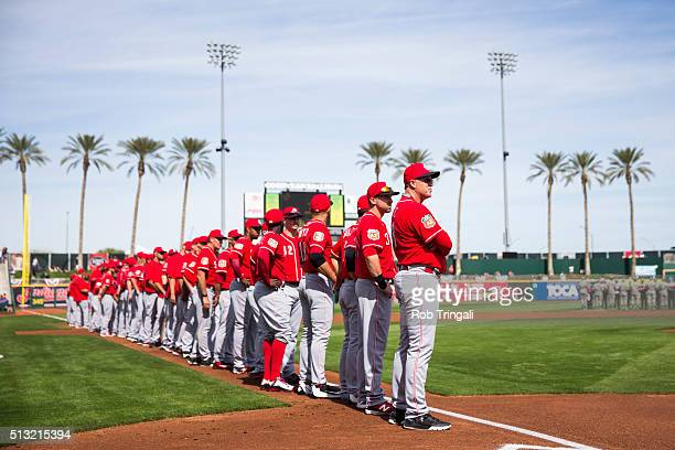 Members of the Cincinnati Reds look on before the first spring training game of the season against the Cleveland Indians at Goodyear Ballpark on...