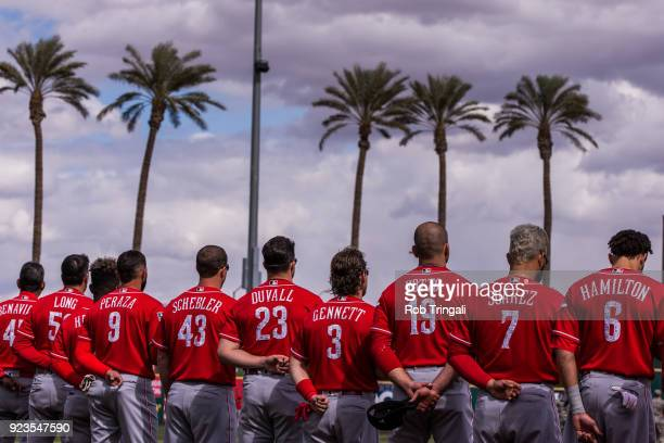 Members of the Cincinnati Reds stand for the National Anthem before a game against the Cleveland Indians during a Spring Training Game at Goodyear...