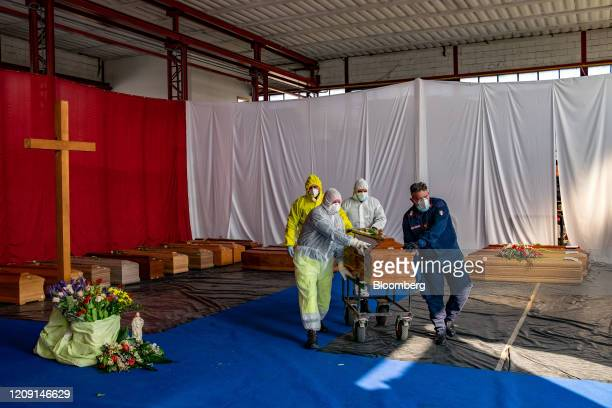 Members of the civil protection and Carabinieri, transport a coffin, containing a victim of coronavirus, from a re-purposed warehouse of a road...