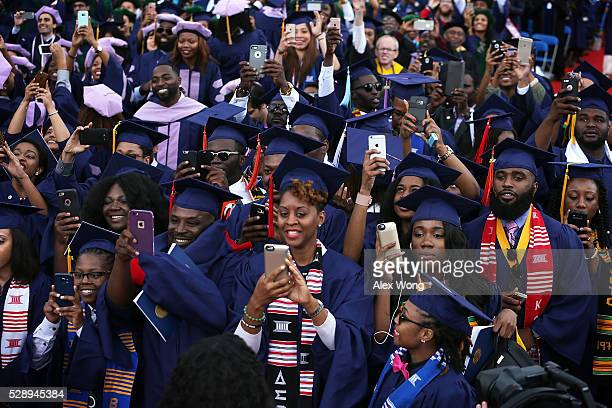 Members of the class of 2016 take pictures with their smartphones as US President Barack Obama addresses the 2016 commencement ceremony at Howard...