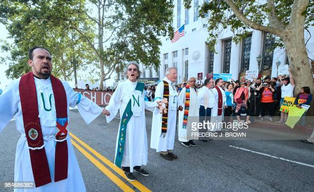 Members of the clergy from different denominations hold hands as they block the road in front of the Federal Building ahead of their arrest in an act...