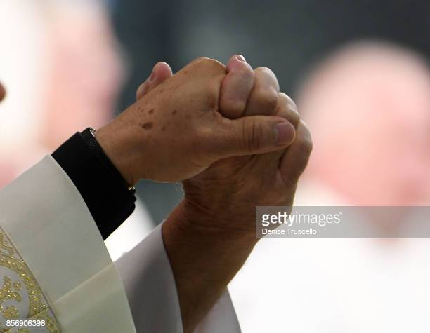 Members of the clergy hold hands during a vigil at Guardian Angel Cathedral for the victims of the Route 91 Harvest country music festival shootings...