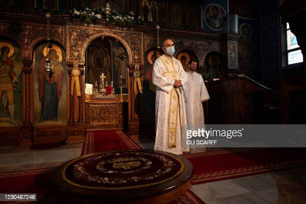 Members of the clergy queue to receive confession from Serbian Orthodox Christian priest, Father Nenad Popovic during a service of the Nativity of...