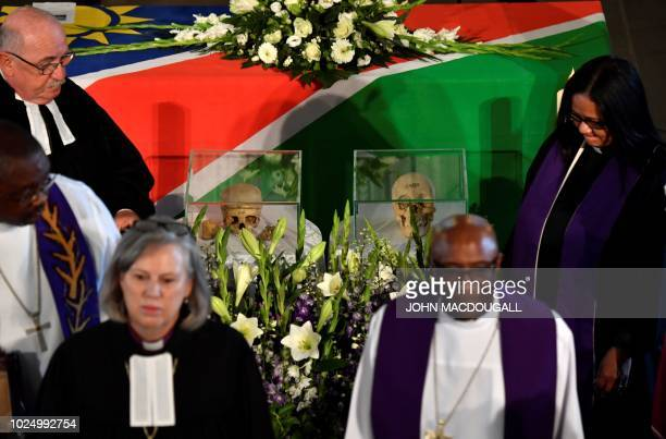 Members of the clergy walk past two skulls displayed during a handing-over ceremony of human remains that were brought to Berlin during its colonial...