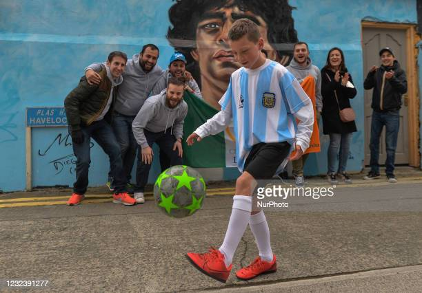 Members of the Club Napoli Dublin watch Johnny Figo Murphy, age 9, showing off his soccer skils in front of a new mural by CHELS , representing Diego...