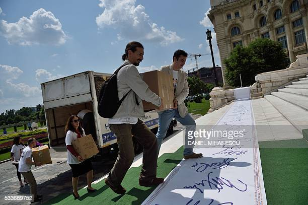 Members of The Coalition for the Family NGO carrie boxes with collected signatures to the Romanian Senate in Bucharest Romania on May 23 2016 Several...
