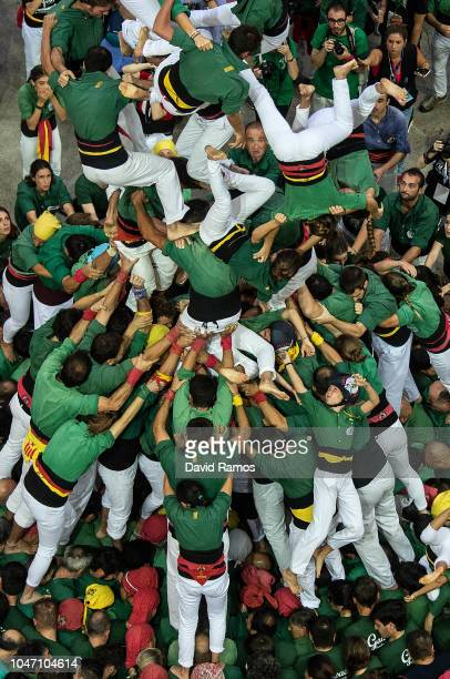 Members of the colla Castellers de Sabadells fall down as they build a human tower during the 27th Concurs de Castells competition on October 7 2018...