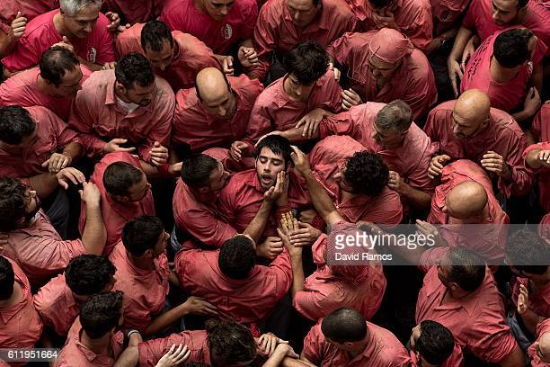 Members of the colla 'Vella de Valls' helps a team mate after falling down as they built a human tower during the 26th Tarragona Competition on...