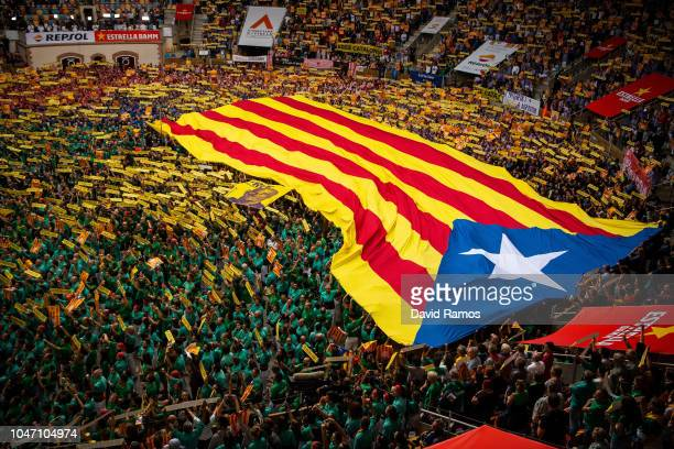 Members of the collas sing the Catalan National Anthem 'Els Segadors' as they display an Independence flag during the 27th Concurs de Castells...