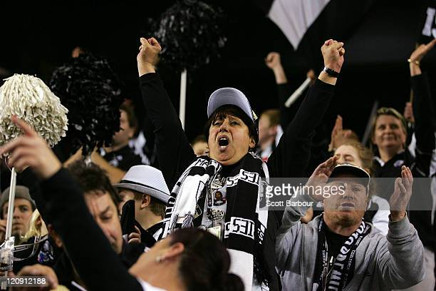 Members of the Collingwood cheer squad show their support during the round 21 AFL match between the St Kilda Saints and the Collingwood Magpies at...
