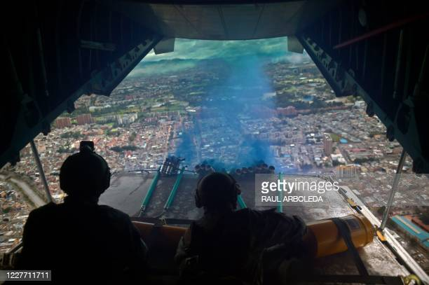 Members of the Colombian Air Force shoot blue smoke from a CASA C-295 aircraft flying over Bogota, during the 210th anniversary of the country's...