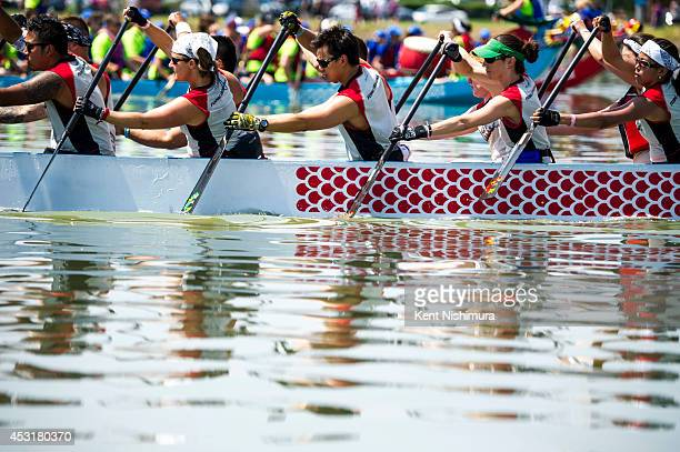 members of the Colorado Flying Dragons paddle out to the race staging area during the 2014 Colorado Dragon Boat Festival at Sloans Lake Park on...