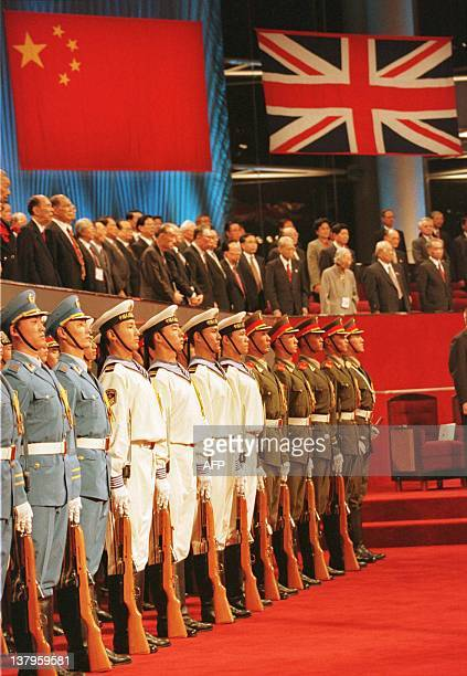 Members of the combined forces of the Chinese Armed Forces stand to attention under the Chinese and British flags during the ceremony marking the...