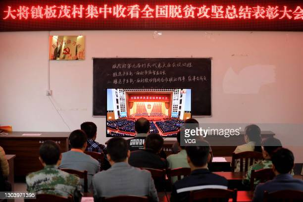 Members of the Communist Party of China watch a television screen broadcasting a grand gathering held at the Great Hall of the People to mark the...