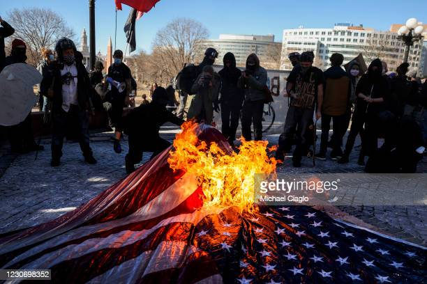 Members of the Communist Party USA and other anti-fascist groups burn an American flag on the steps of the Colorado State Capitol on January 20, 2021...