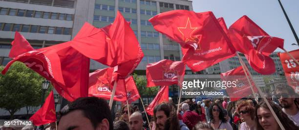 Members of the Communist Youth hoist red flags while walking through Avenida da Liberdade during the parade to celebrate the 44th Anniversary of the...