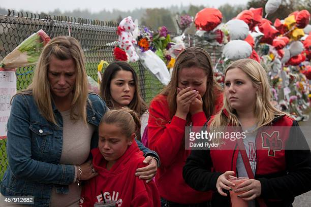 Members of the community and students grieve beside a makeshift memorial at MarysvillePilchuck High School on October 26 2014 in Marysville...