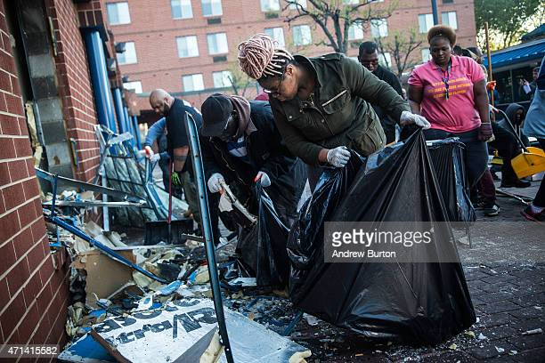 Members of the community clean up debris from a CVS pharmacy that was set on fire yesterday during rioting after the funeral of Freddie Gray on April...