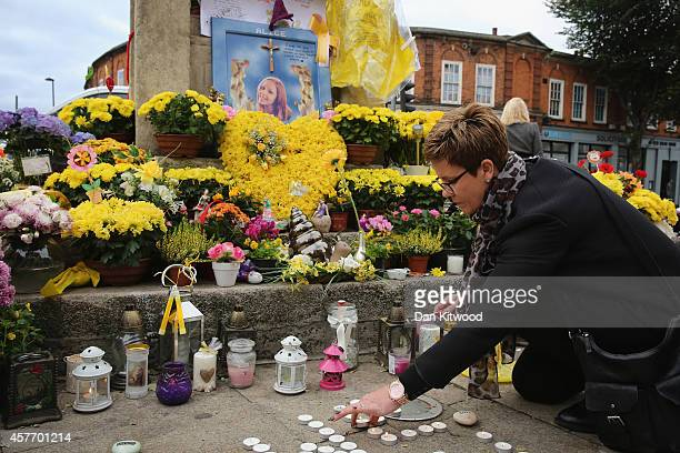 Members of the community light candles and place them besides the clock tower in Hanwell ahead of the funeral for murdered teenager Alice Gross on...