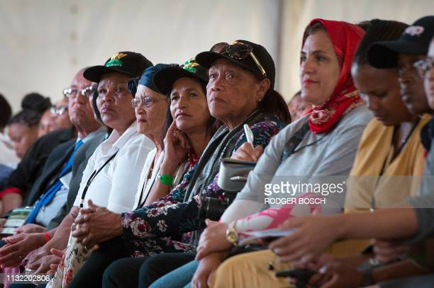 Members of the community listen as the president of South Africa addresses a public meeting where the South African government is returning land lost...