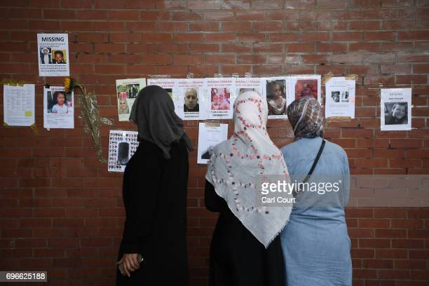 Members of the community look at missing person posters near Grenfell Tower on June 16 2017 in London England 30 people have been confirmed dead and...