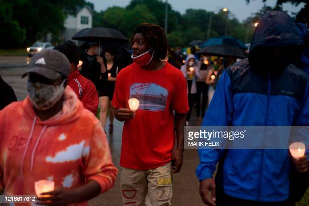 Members of the community march as they mourn the death of George Floyd during a candle light vigil at Resurrection Metropolitan Community Church in...