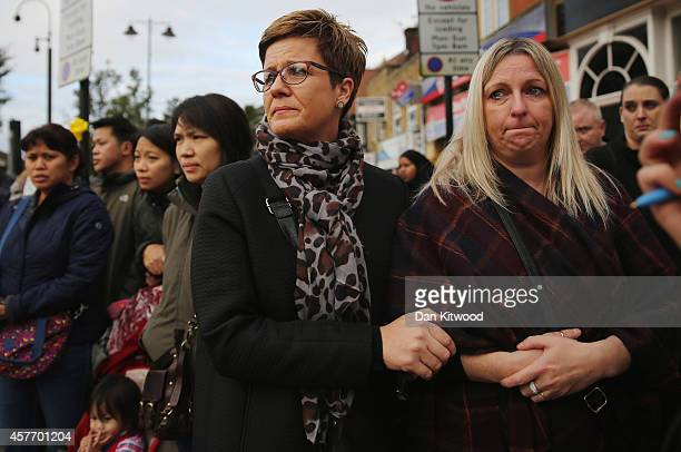 Members of the community watch as the funeral cortege for murdered teenager Alice Gross passes through Hanwell town centre on October 23 2014 in...