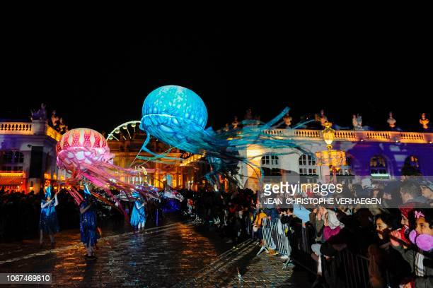 Members of the Compagnie Planete Vapeur hold flying jellyfish balloons as they perform during the parade of the festivities of Saint Nicholas in...