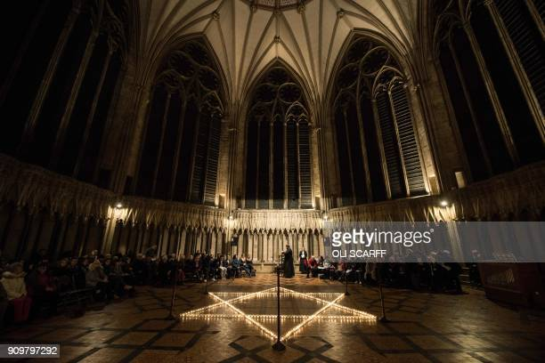 Members of the congregation are seated around 600 candles depicting the Star of David set out during an event to commemorate Holocaust Memorial Day...