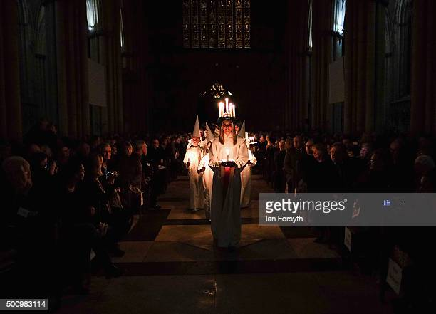 Members of the congregation look on as Sara Kjorling from Stockholm leads the procession during the traditional Swedish festival of Sankta Lucia at...
