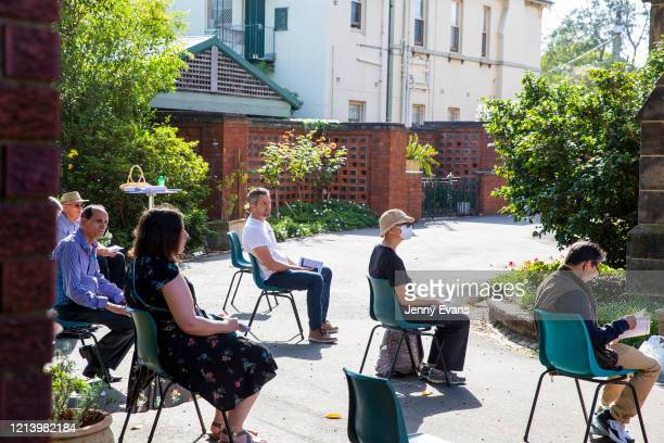 Members of the congregation look on at a service held in the yard of St Paul's Anglican Church in Burwood with seating observant of social distancing...
