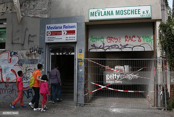 Members of the congregation of the Mevlana Mosque arrive for prayer next to a blockedoff side entrance to the building leading to a back section that...