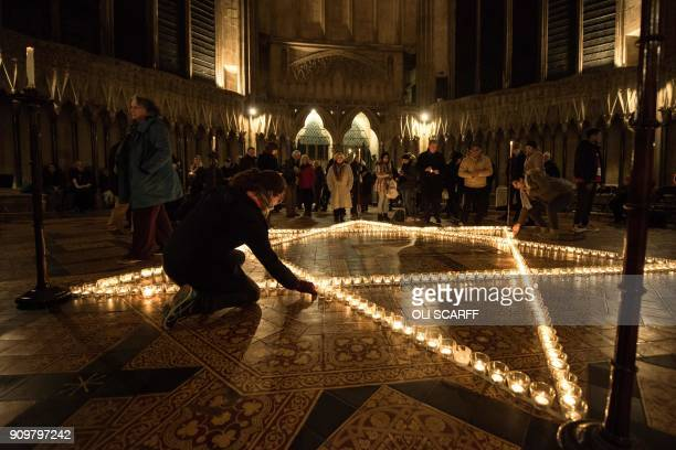 Members of the congregation place lit candles amongst 600 candles depicting the Star of David set out during an event to commemorate Holocaust...