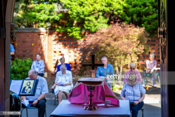 Members of the congregation pray at a service held in the yard of St Paul's Anglican Church in Burwood with seating observant of social distancing on...