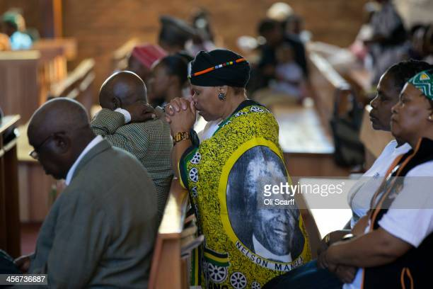 Members of the congregation pray in Regina Mundi Catholic Church in Soweto Township as the funeral of former South African President takes place in...